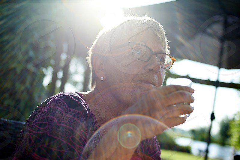 Affluent elderly woman sitting in her garden in summer sunshine enjoying a little glass of liquor photo
