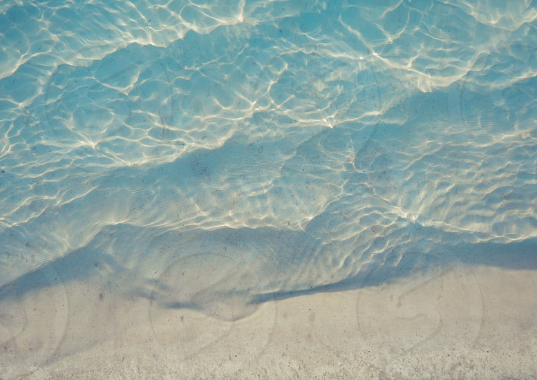 Swimming pool rippled water detail with marble step under water photo