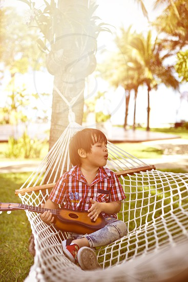 Candid portrait of a young mixed race Asian boy playing guitar outdoor 3 photo