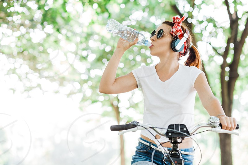 Young woman drinking water sitting on the bicycle photo