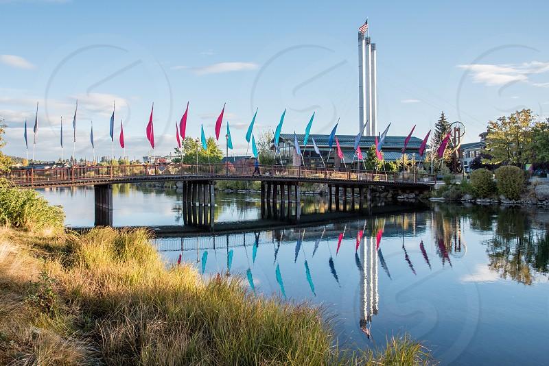 Bend Oregon old mill smoke stacks river Deschutes bridge flags photo