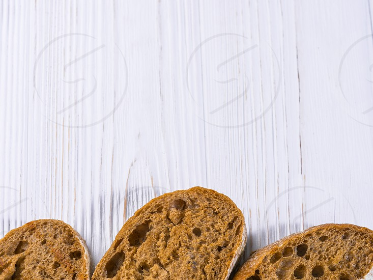 Wholemeal bread slices isolated on white wooden shabby table background. Frame photo. Copy space. photo