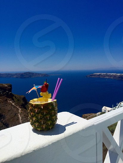 pineapple fruit parfait placed on white handrail overlooking sea during daytime photo
