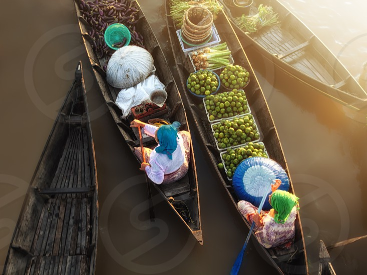 people riding brown canoe boats carrying assorted vegetables floating on brown water during daytime photo