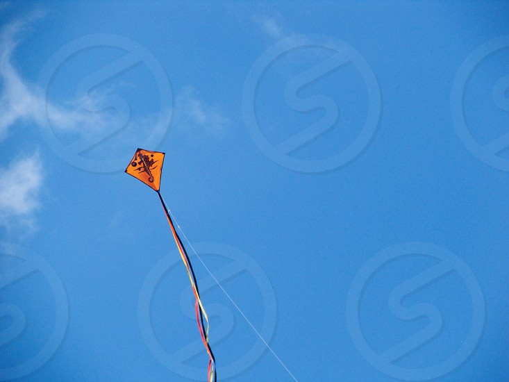 Black print yellow kite in the blue sky photo