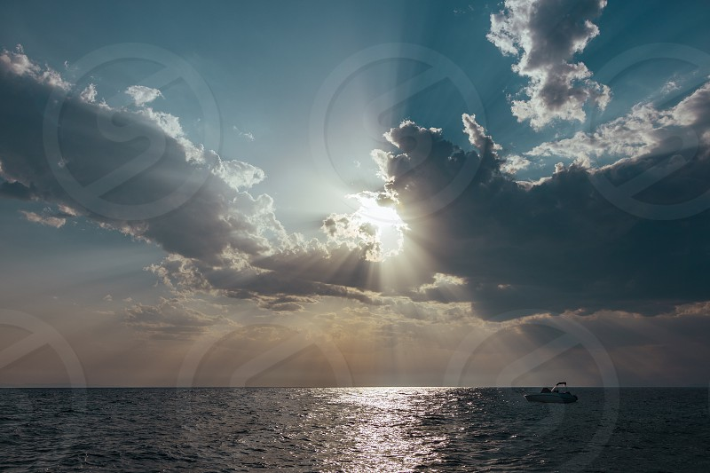 Sun breaking through the clouds on the sea photo