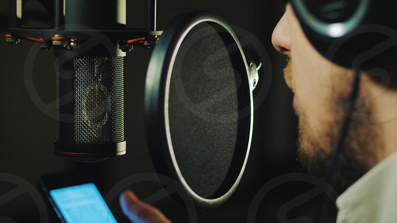 Professional Microphone in recording studio. Man reading rap photo
