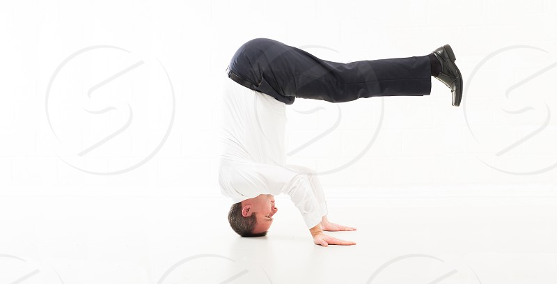 Studio shot of a business man standing on his head taken from a side view on a white back drop photo