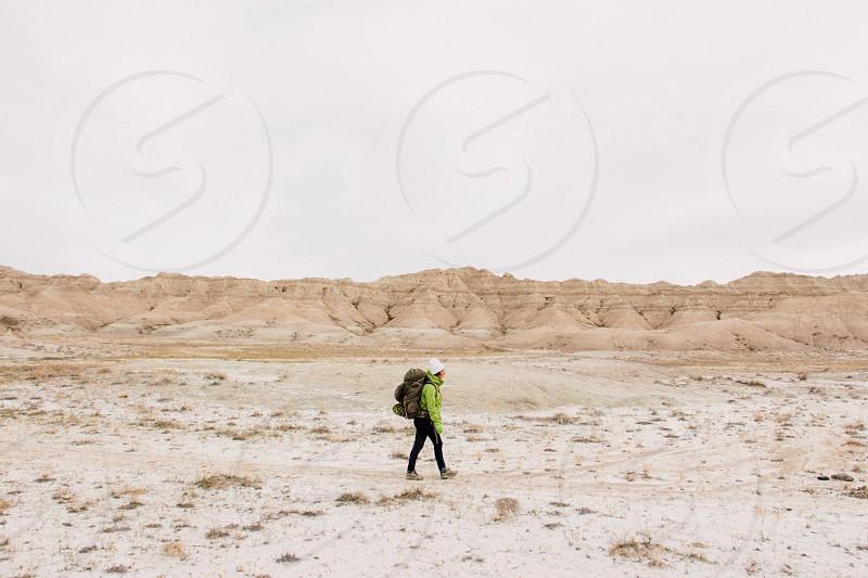 man in green jacket walking on white sands under dark cloudy sky photo