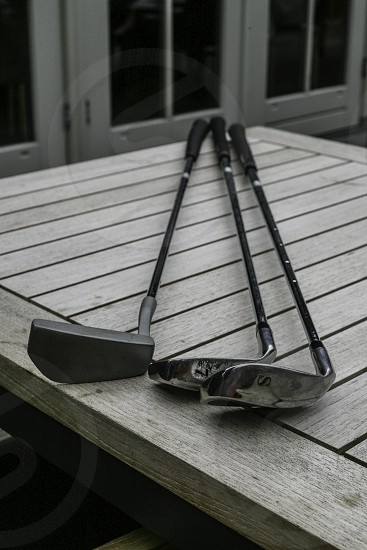 Three golf clubs laying on the table. photo
