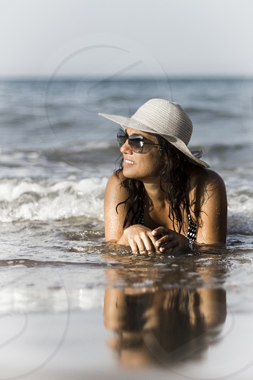 woman in black and white halter bikini top and white sun hat in beach photo
