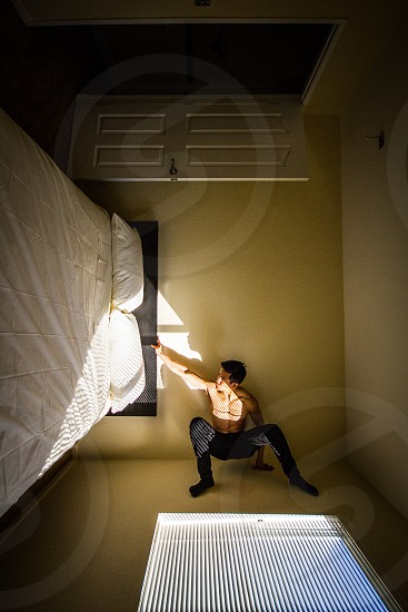 topless man in black pants standing on the wall over the bed photo