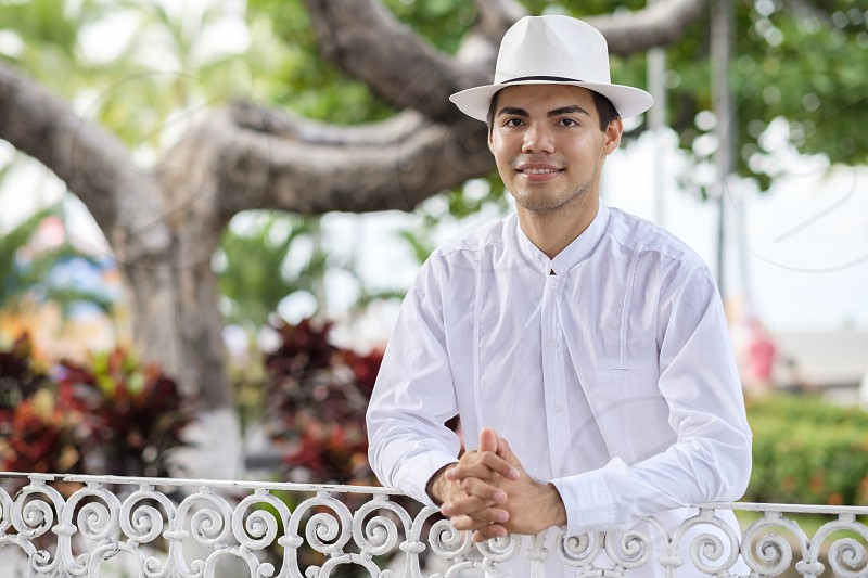 Young hispanic man in formal clothes wearing white shirt pants and hat smiling at camera. photo
