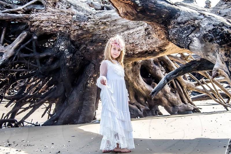 girl in white dress near driftwood photo