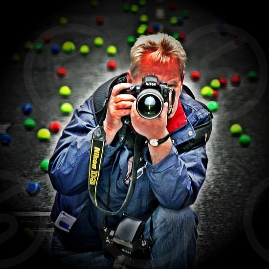 man taking a photo using a black dslr camera photo