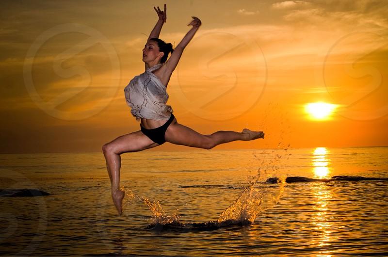 woman in white halter top and black bikini bottom dancing on blue ocean water under orange sunset photo