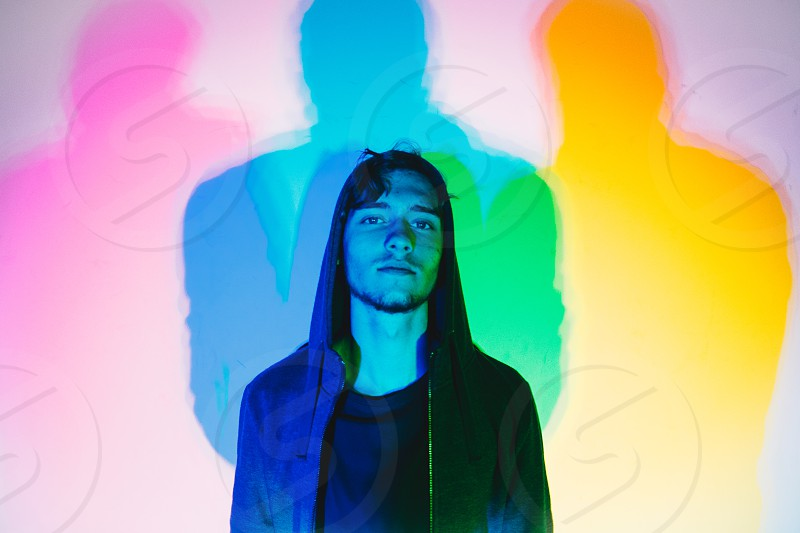 Portrait of a man wearing a hoodie standing in front of a wall lit up by color lights. photo