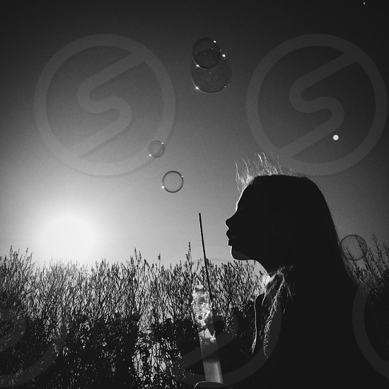 Girl blowing bubbles photo