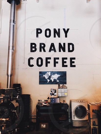 pony brand coffee black text sign on white wall photo