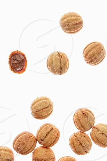 Food pattern with freshly baked homemade cakes in a shape of walnuts filled a condensed milk cream on a white background copy space. photo