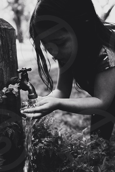girl drinking on the faucet photo