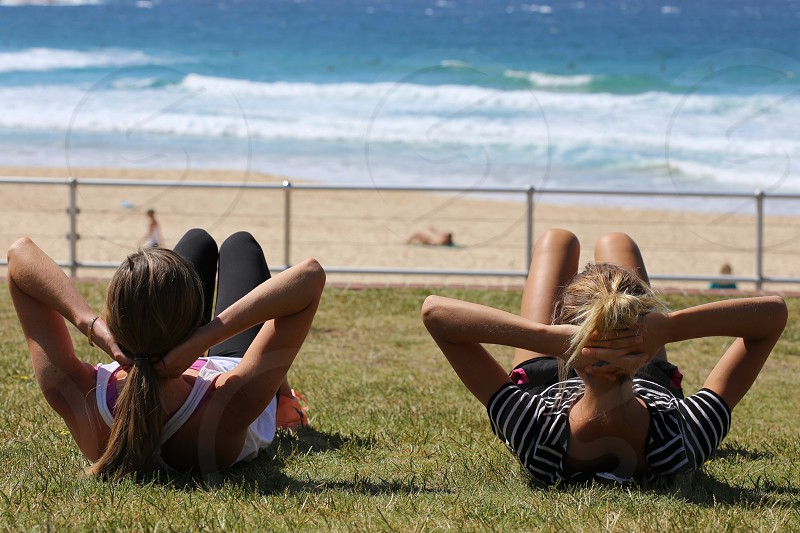 2 ladies exercising on the green grass photo