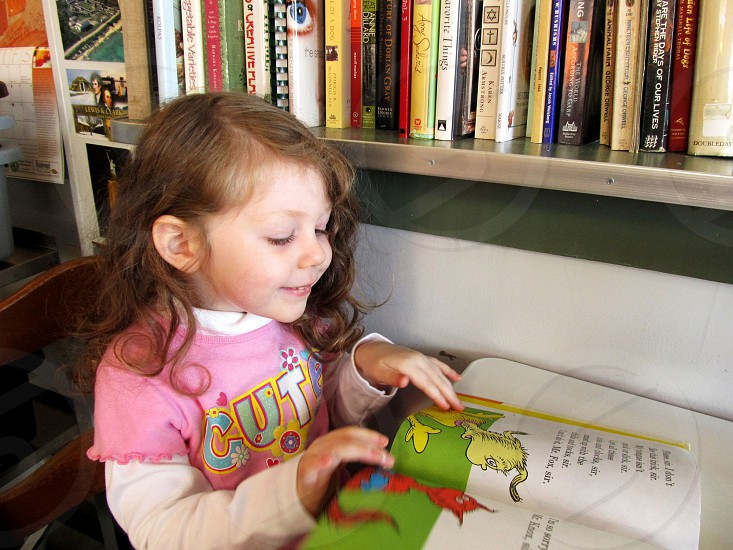 Little girl in pink shirt reading a book next to a shelf full of books photo