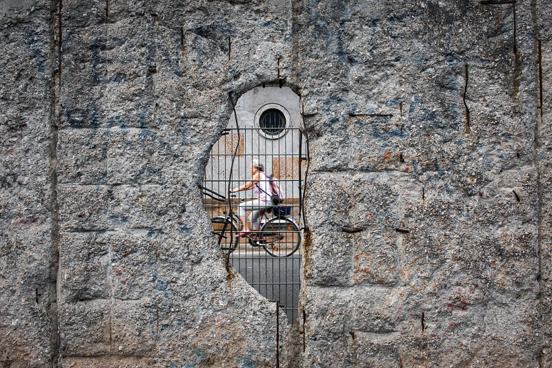 Cyclist passing a gap in the Berlin Wall. photo