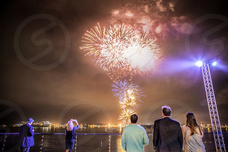 Watching fireworks over the ocean. Water party celebration explosion. photo