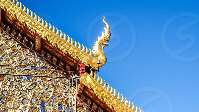yellow gold spiked dragon along roof lines of blue and gold temple against blue sky photo