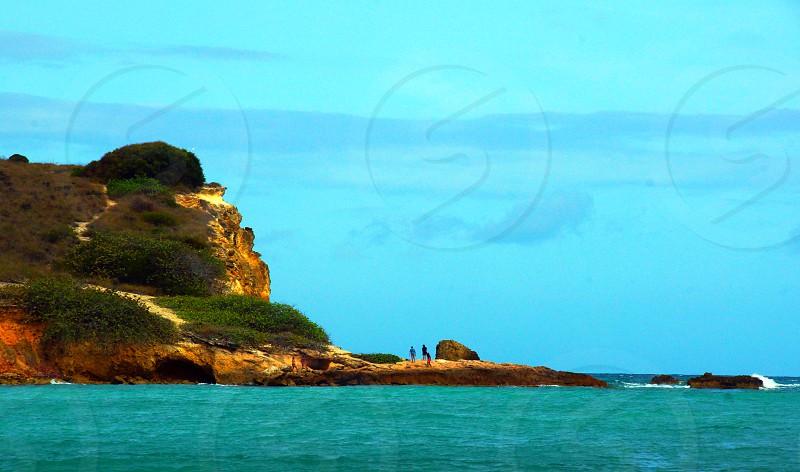 3 people walking on island photo