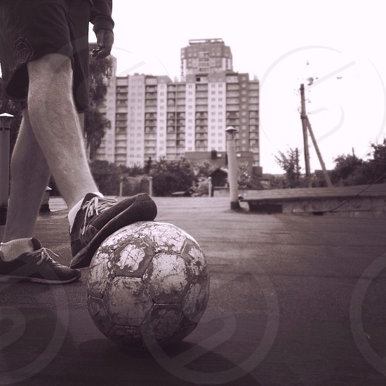 man resting foot on soccer ball photo