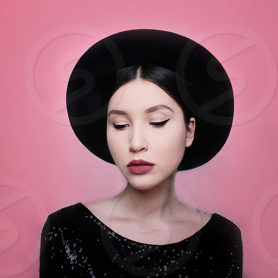 Portrait of beautiful sexy awesome girl in black hat and dress in pink background photo