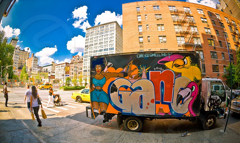 People walking by an old truck covered in graffiti on the streets of New York photo