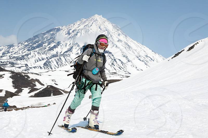 AVACHA VOLCANO KAMCHATKA PENINSULA RUSSIA - APRIL 21 2012: Open Cup of Russia on Ski-Mountaineering on Kamchatka - young woman ski mountaineer climb on mountain on background Koryak Volcano. photo