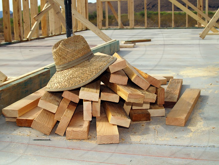 A weaved hat sitting on a pile of lumber at a construction site. photo