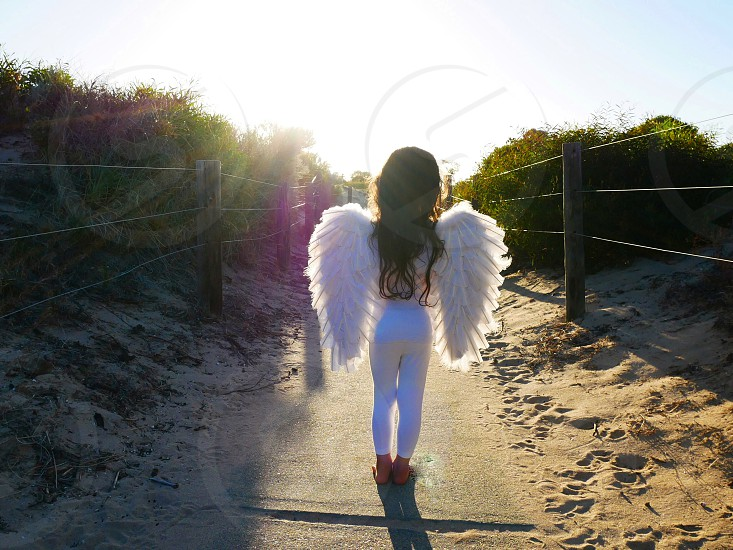 Silhouette angel white wings girl sand beach photo