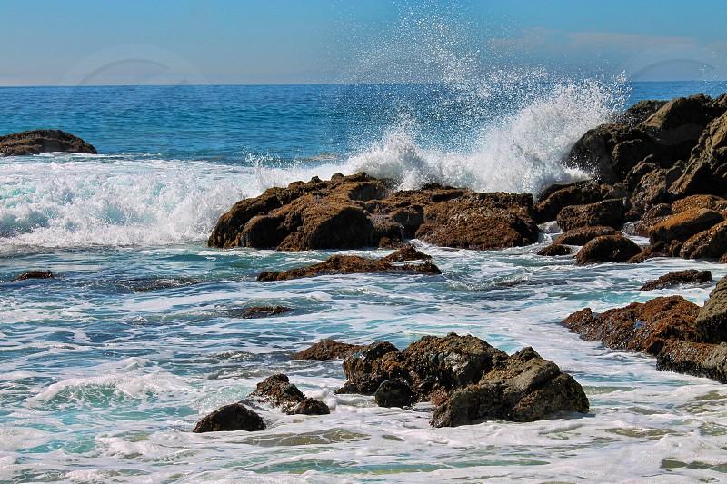 Ocean waves crashing onto a rocky shore photo