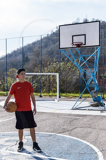 Boy standing on the basketball court with ball in his hand photo