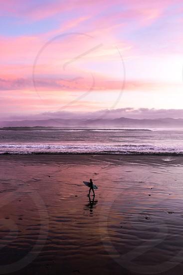 Surfer walking on beach during Sunset. photo