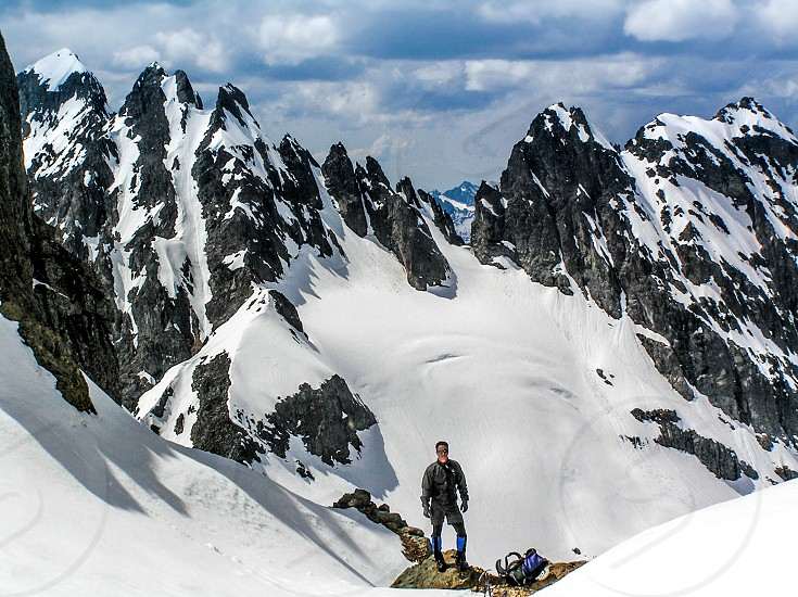 man in black jacket standing on mountain covered in snow during daytime photo