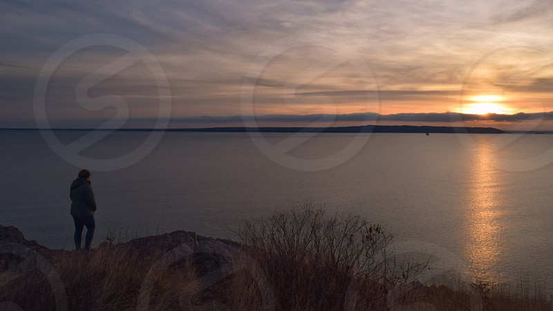 Sunset over lake superior with a person admiring the sunset at a distance photo
