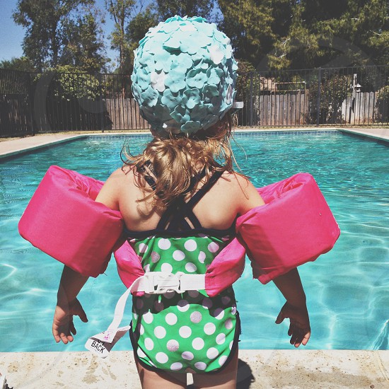 children's green and white polka dot one piece swimsuit with blue floral swim cap and pink water wings photo