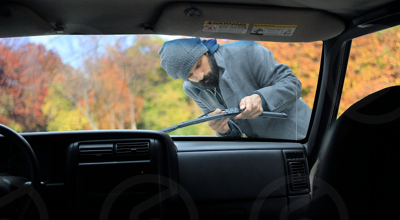 man in grey jacket and grey beanie hat fixing windshield wiper photo