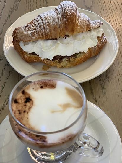 Morettocappuccinoespresso coffeemorninggood morningcroissantcreamchocolatepowdered sugarmilk foam baritalyitalianfoodrelaxsweet photo
