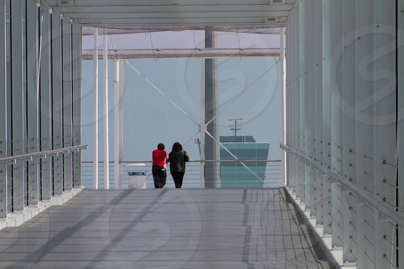 two people crossing a bridge photo