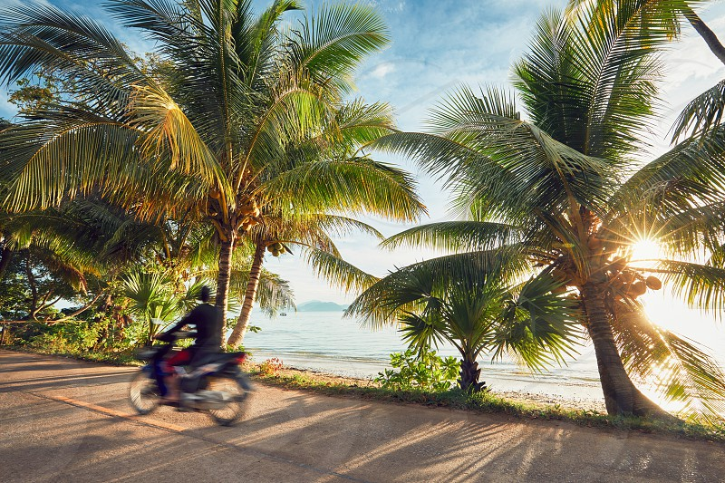 Tourist is driving motorbike on the tropical island at the sunrise. Koh Yao Noi Thailand photo