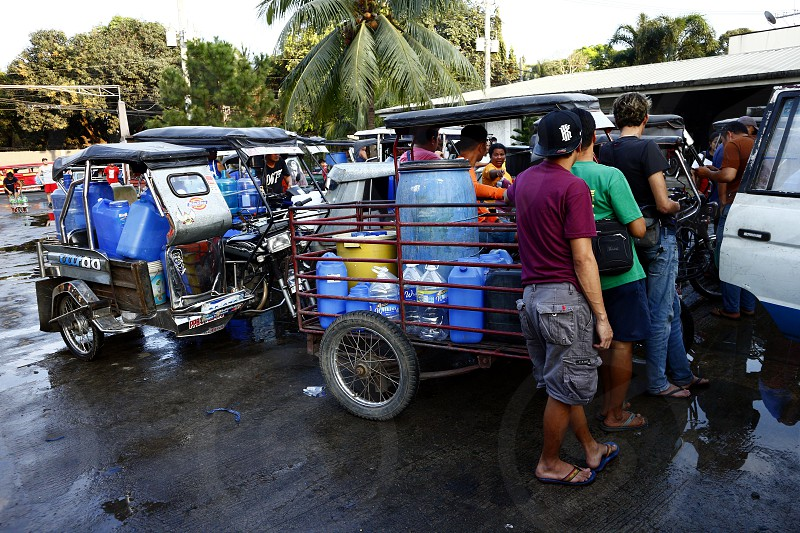 ANTIPOLO CITY PHILIPPINES - MARCH 14 2019: Residents line up with their containers to get deep well water from an alternate filling station due to a shortage in water supply which lasted for days. photo
