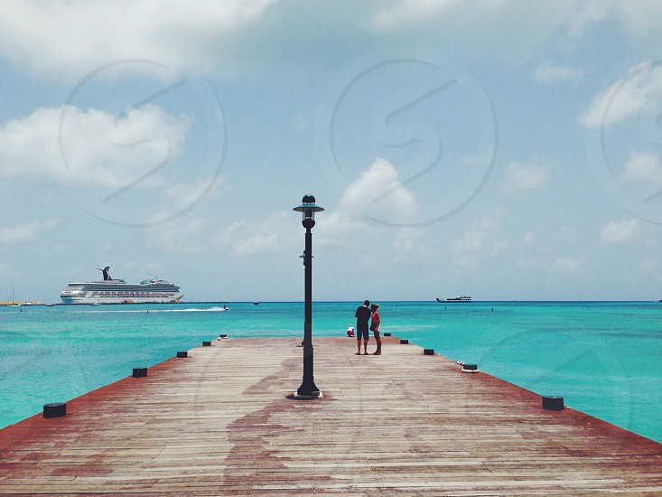 two person on brown wooden dock photo