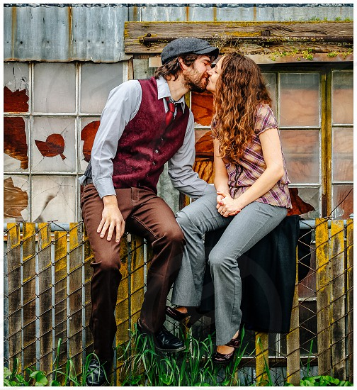couple kissing while sitting on metal fence photo
